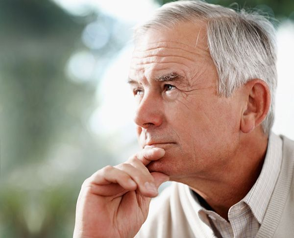 older man looks off into the distance with hand on chin