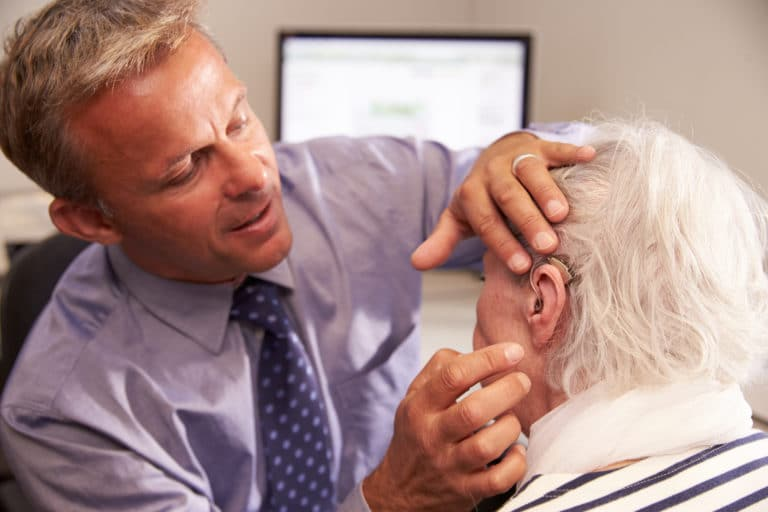 Audiologist fitting a senior female patient with a hearing aid