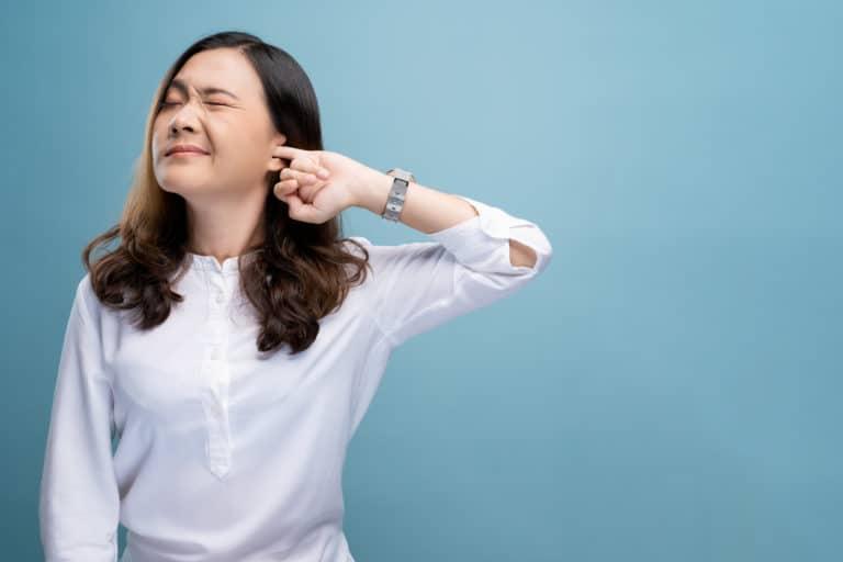 Woman putting finger in ear